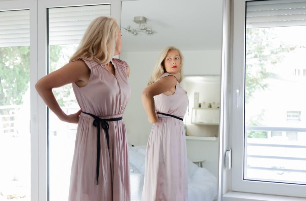 Woman looking into a full-length mirror disappointed in her stubborn fat areas