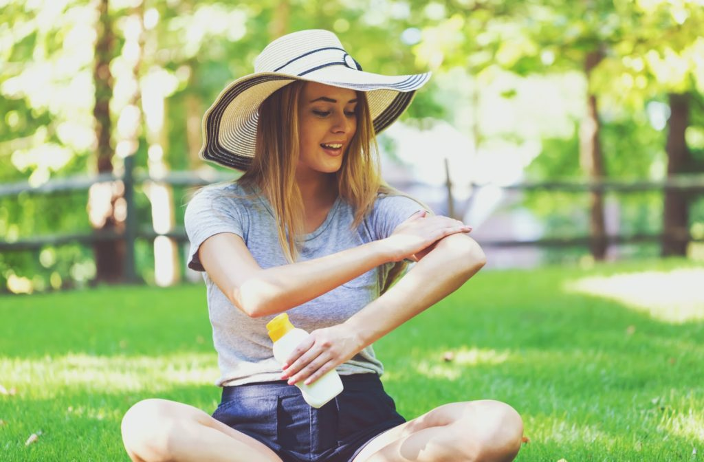 young woman wearing a wide brimmed floppy hat sitting in the grass applying a cream sunscreen to her left arm