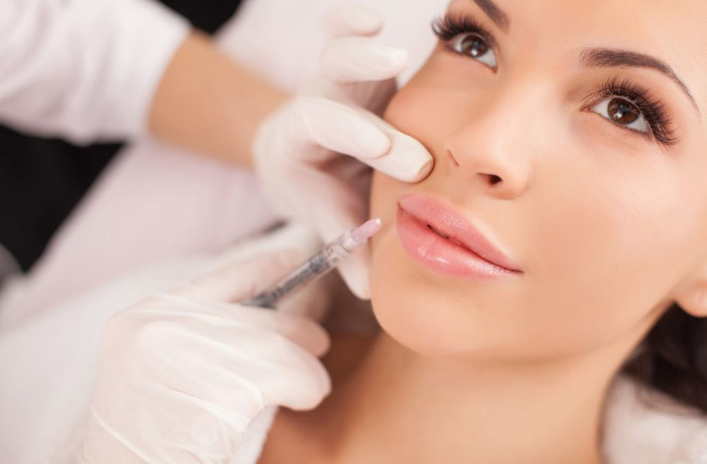 Young happy woman receiving botox lip filler from professional.