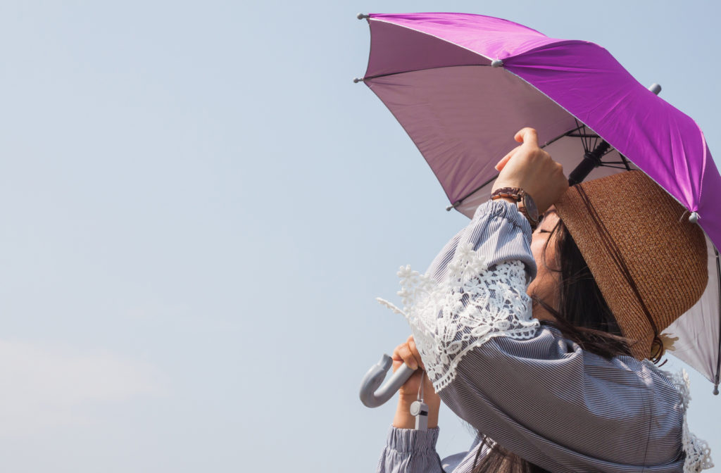 Woman holding umbrella and wearing long sleeve shirt to avoid sunlight